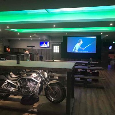 Green neon lighting over pool tables at The Ball Room Meadowbank
