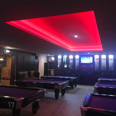 Red neon lighting over pool tables